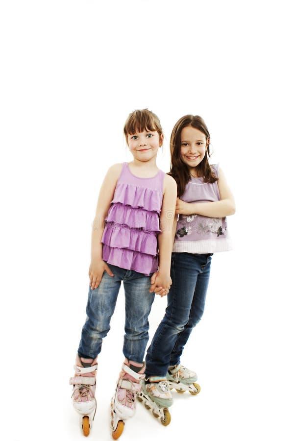 Zwei nette Mädchen, welche die Hände tragen Rollenrochen anhalten lizenzfreie stockfotos