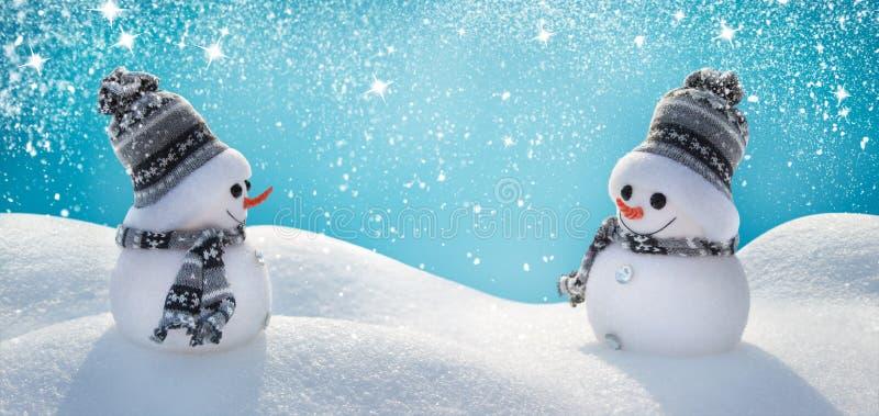 Zwei nette Schneemänner, die in einer Winter Weihnachtslandschaft stehen stockbild