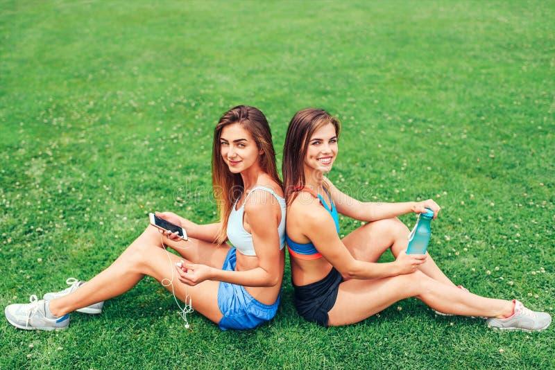 Zwei nette sportliche Mädchen, die nach dem Training im Freien sich entspannen stockfotos