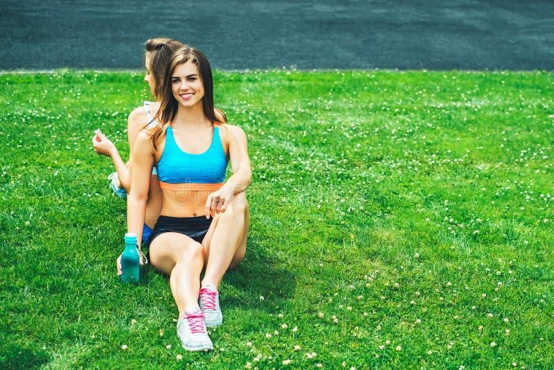 Zwei nette sportliche Mädchen, die nach dem Training im Freien sich entspannen lizenzfreies stockbild