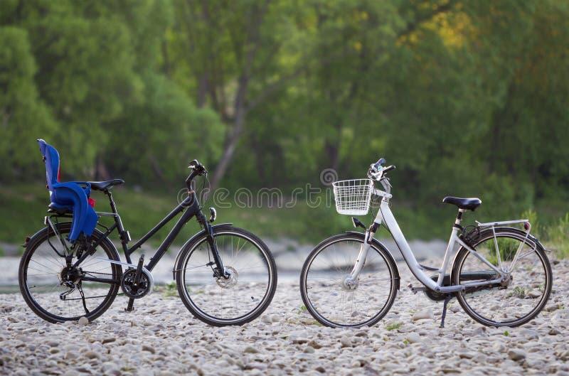 Zwei neue moderne Fahrräder: schwärzen Sie mit blauem Plastikkindersitz und -WEISS mit dem Korb, der an durch Sonnenkiesel auf un stockbild