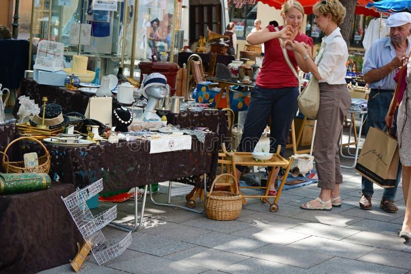 Zwei nicht identifizierte Frauen schließen einen Kauf an einer Flohmarkt nahe dem Stadtzentrum ab Nur Leitartikel lizenzfreie stockfotografie