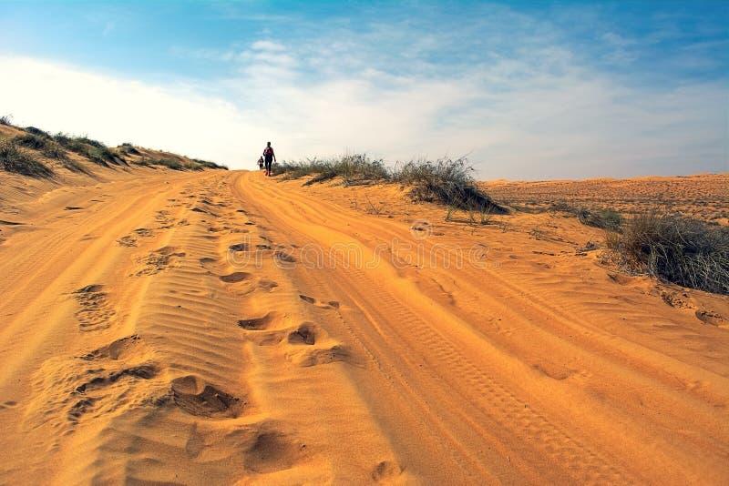 Zwei nicht identifizierte Läufer, die in Wüste im Sonnenaufgang laufen lizenzfreie stockfotos