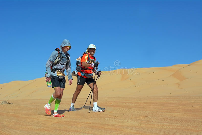 Zwei nicht identifizierte Läufer, die in Wahiba-Wüste laufen stockfoto