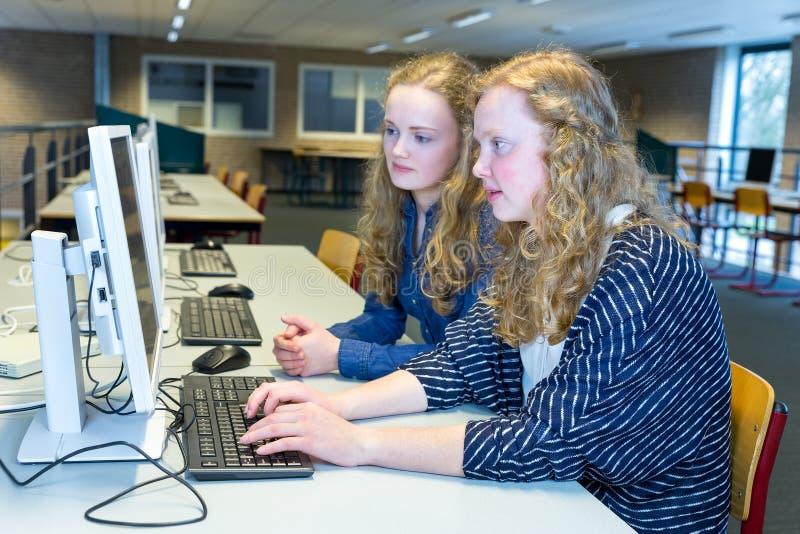 Zwei niederländische Studenten, die an Computer in der Schule arbeiten stockfotografie
