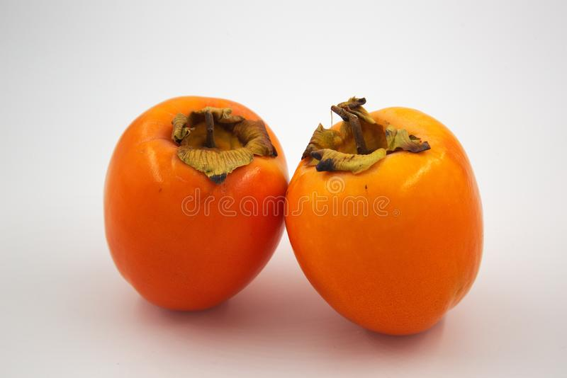 Zwei orange Kakipflaumenbaum-Persimone stockfotos