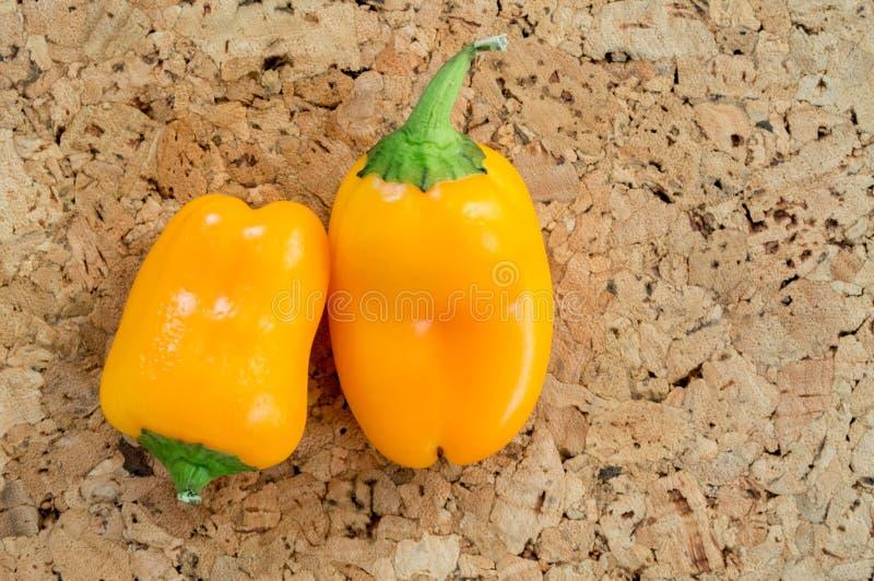 Zwei orange Minigemüsepaprikas auf einem braunen Korkenhintergrund lizenzfreies stockbild