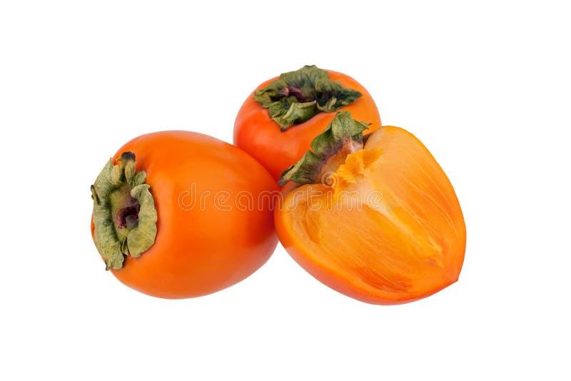 Zwei orange Persimonefrüchte oder Diospyros und eine abgeschnittene Hälfte der Persimone mit grünen Blättern auf weißer Hintergru lizenzfreie stockfotos