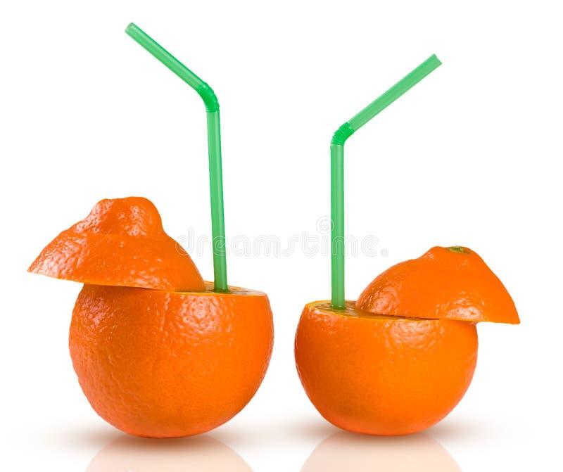 Zwei Orangen mit grünem coctail Stroh lokalisiert auf weißem Hintergrund stockbild