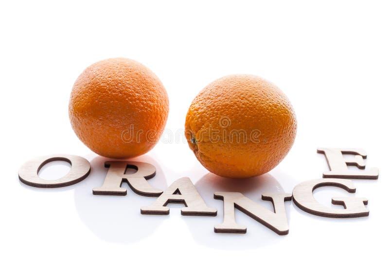 Zwei Orangen und die Wort Orange Lokalisierte Zusammensetzung auf weißem Hintergrund mit Schatten lizenzfreie stockfotografie