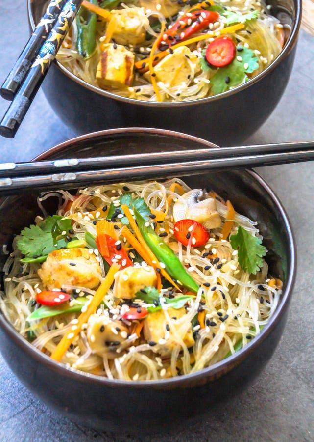 Zwei orientalische Platten mit einem Teller des strengen Vegetariers von Glasnudeln, von Tofu und von Frischgemüse lizenzfreie stockfotos