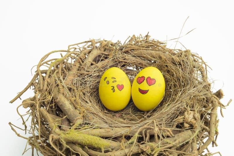 Zwei Ostereier gemalt mit emojis, eins in der Liebe und anderes Küssen, gesetzt in ein Nest in lokalisiertem weißem Hintergrund lizenzfreies stockfoto
