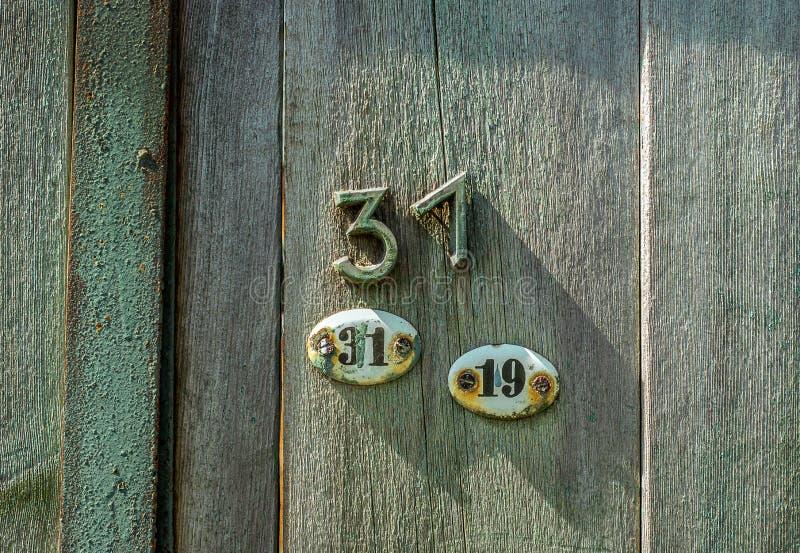 Zwei ovale Metallplatten mit nubers dreißig eins und neunzehn und Nr. dreißig eins genagelt auf hölzerner Tür stockbilder