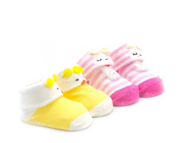 Zwei Paare der gelben und rosa Farbe der Babysocke stockfoto