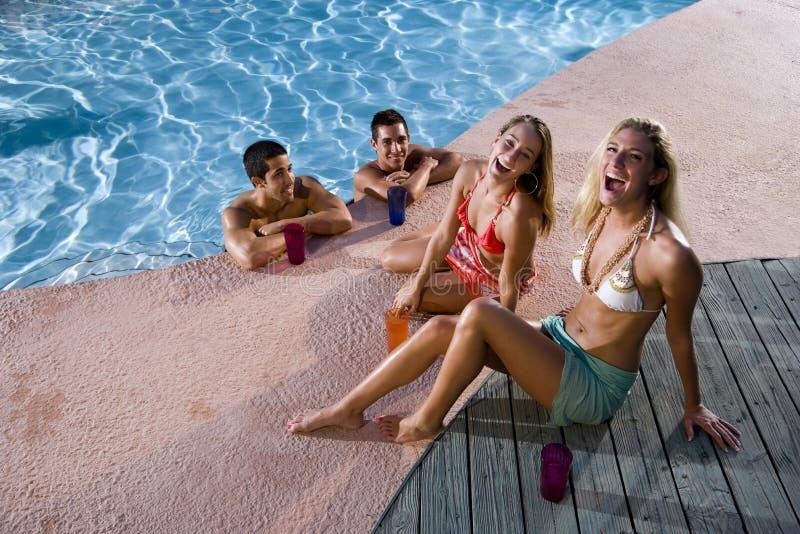 Zwei Paare, die heraus an der Swimmingpoolplattform hängen lizenzfreie stockfotos