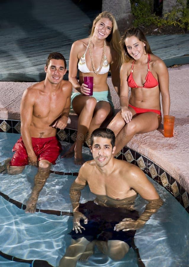 Zwei Paare, die heraus im Swimmingpool hängen lizenzfreies stockbild