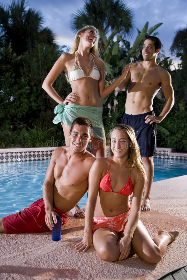 Zwei Paare, die heraus im Swimmingpool hängen lizenzfreie stockfotografie
