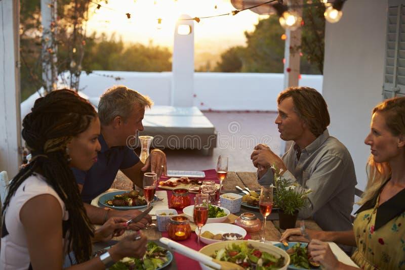 Zwei Paare, die oben Abendessen auf einer Dachterrasse, Abschluss essen stockbilder