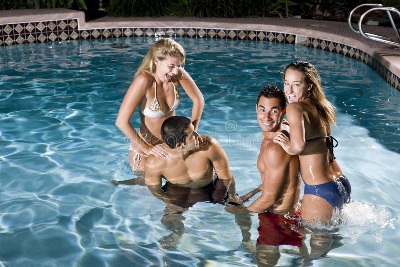 Zwei Paare im Swimmingpool nachts stockbilder