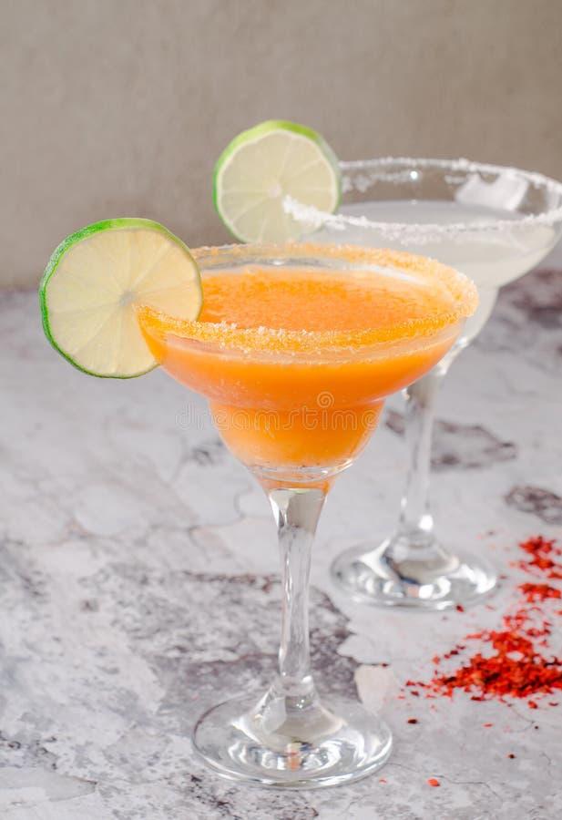 Zwei perfektes Klassiker und Mango Margarita-, weißes und Orangealkoholisches Cocktail mit Dekoration des Salzes am Rand lizenzfreie stockfotografie