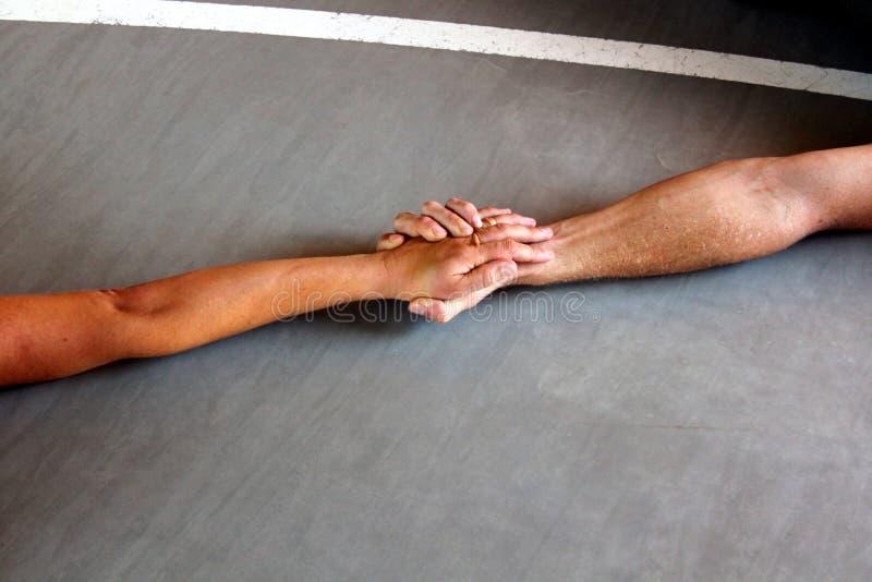 Zwei Personenhändchenhalten auf dem Boden lizenzfreie stockfotos