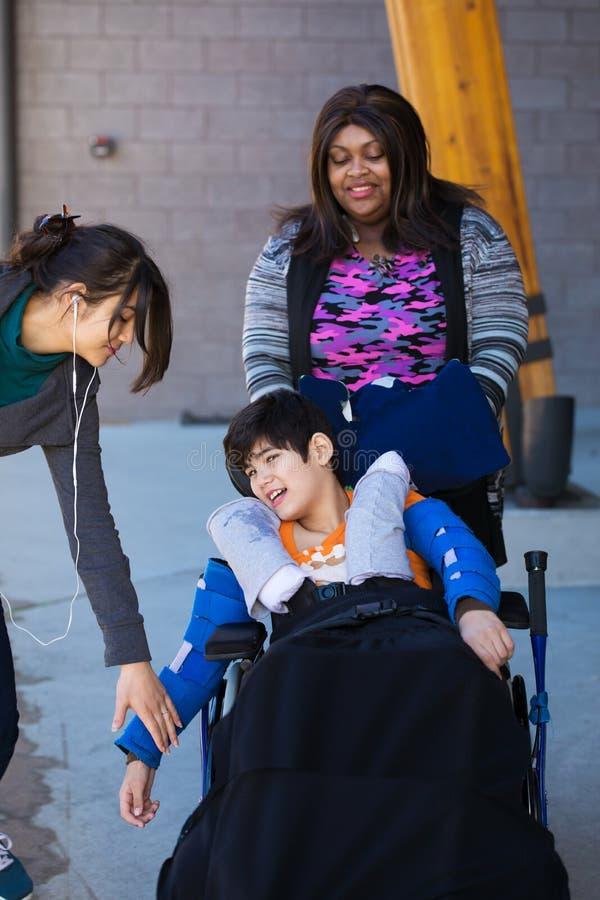 Zwei Pflegekräfte, die um behindertem Jungen im Rollstuhl im Freien sich kümmern stockfoto