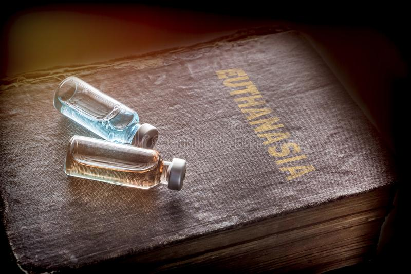 Zwei Phiolen mit Medizin auf einem alten Buch der Euthanasie, lizenzfreie stockfotos