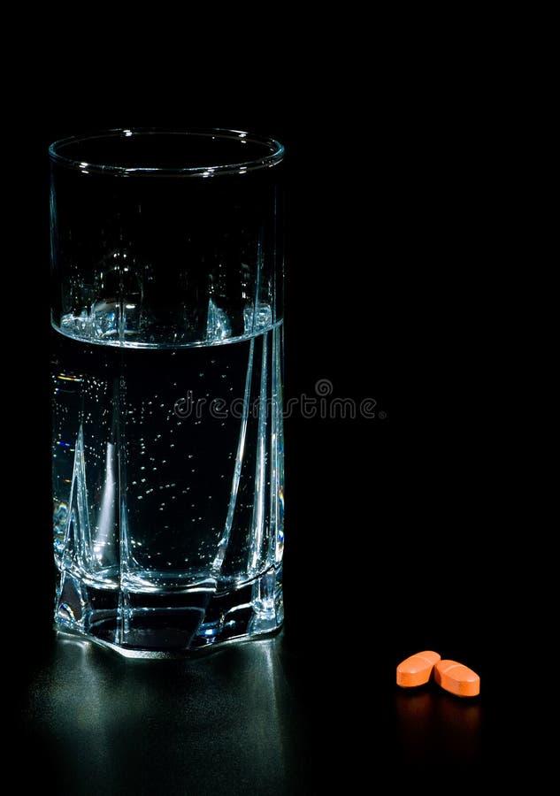 Zwei Pillen und Glas Wasser stockfotos