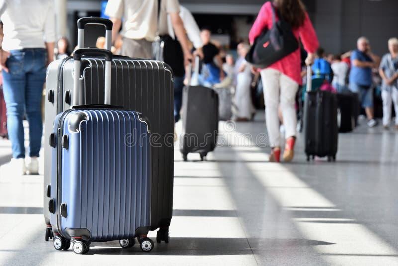 Zwei Plastikreisekoffer in der Flughafenhalle stockfotos