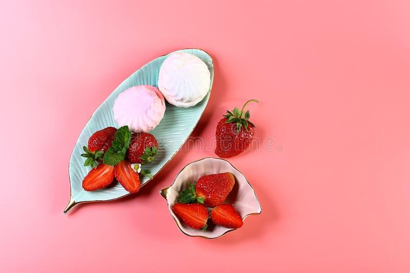 Zwei platesof Eibische und frische Erdbeeren, lokalisiert auf rosa Hintergrund mit Kopienraum Ansicht von oben, Satz stockfotos