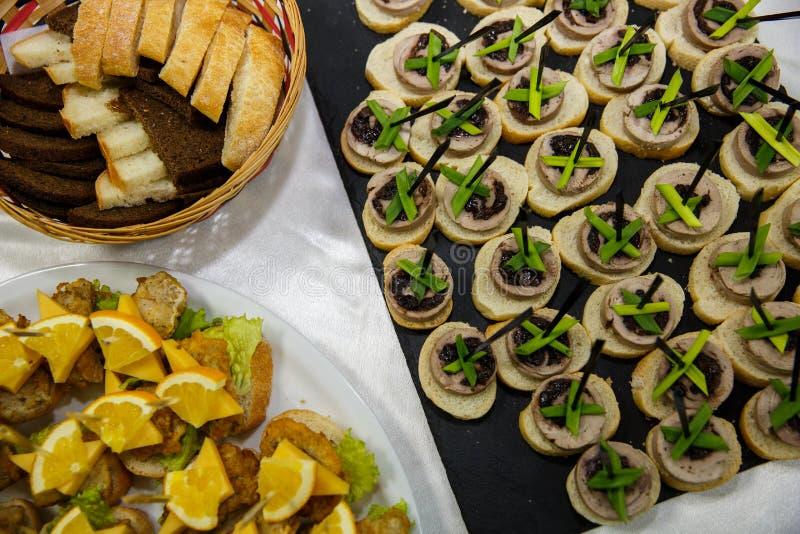 Zwei Platten mit Snäcken auf einem Buffettisch Auswahl des geschmackvollen bruschetta oder der Canapes auf geröstetem Stangenbrot lizenzfreie stockfotos