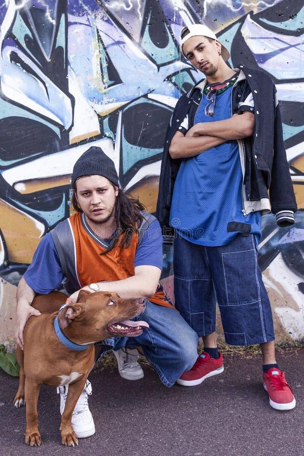 Zwei Pochensänger mit einem Hund in einer U-Bahn mit Graffiti in der Rückseite lizenzfreies stockbild
