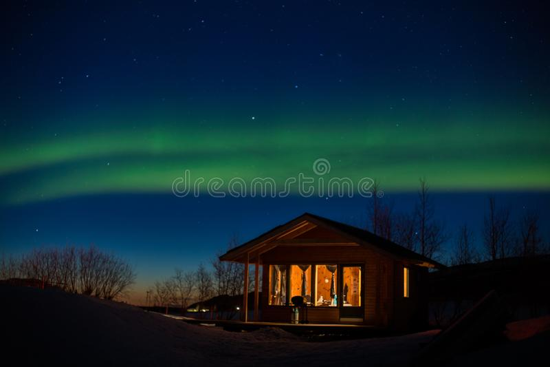 Zwei Polarlichtstreifen über Hütte stockfotos