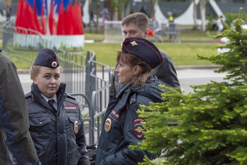 Zwei Polizeimädchen, die auf der Straße mit Männern sprechen lizenzfreie stockfotografie