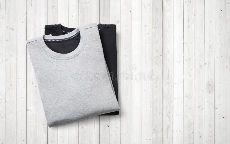Zwei Pullover, die auf weißem hölzernem Hintergrund liegen lizenzfreie stockfotografie