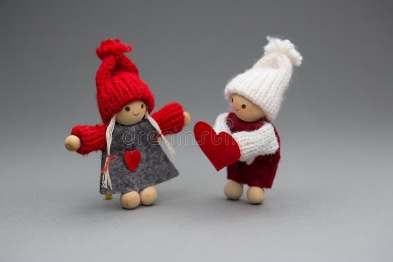 Zwei Puppen in der Liebe auf Valentinsgrußtagesgestrickter Abnutzung mit Herzen stockbilder