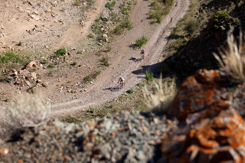 Zwei Radfahrer, die in den Wüstenbergen rasing sind lizenzfreies stockbild