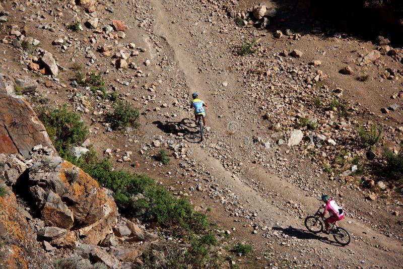 Zwei Radfahrer, die in den Wüstenbergen rasing sind lizenzfreie stockbilder