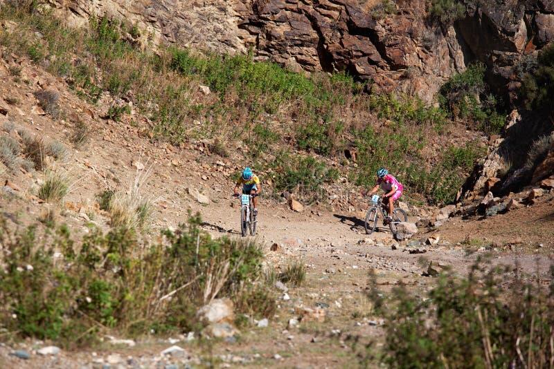 Zwei Radfahrer, die in den Wüstenbergen rasing sind lizenzfreies stockfoto