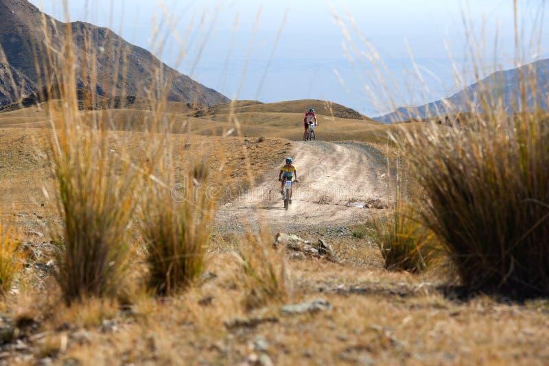 Zwei Radfahrer, die in den Wüstenbergen rasing sind stockfoto