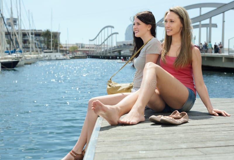 Zwei recht junge Frauen, die auf dem Liegeplatz sitzen lizenzfreie stockfotos