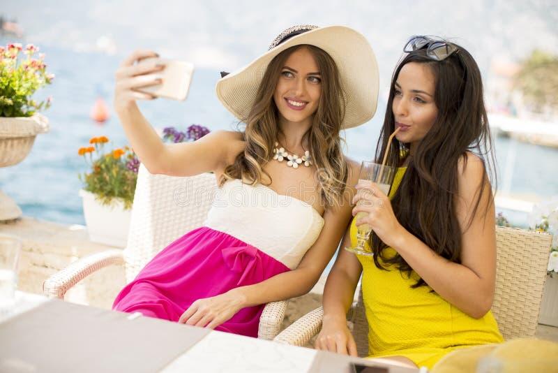 Zwei recht junge Frauen, die selfie mit Handy durch das Se nehmen lizenzfreie stockfotografie