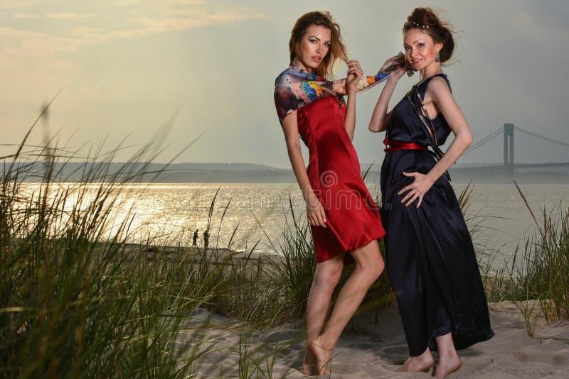 Zwei recht kaukasische junge moderne Frauen, die auf dem Strand in den Luxuskleidern aufwerfen lizenzfreie stockbilder