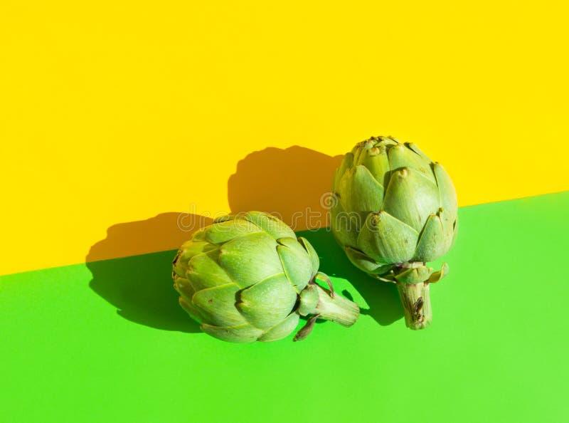 Zwei reife Artischocken auf duotone Gelbgrünhintergrund Harte helle raue Schatten Modische flippige unbedeutende Art Kreative Nah lizenzfreies stockfoto