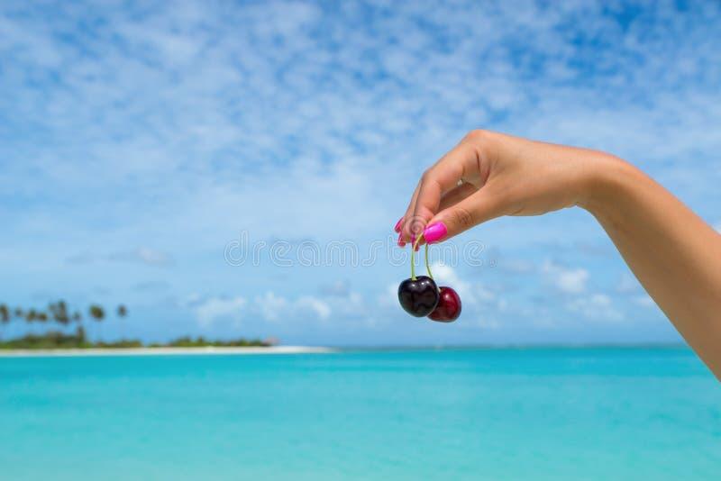 Zwei reife Kirschen auf Frauenhand am tropischen Strand lizenzfreie stockbilder