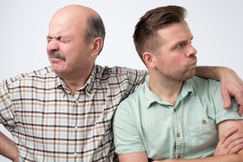 Zwei reife Männer bringen hervor und Sohn werden auf einander beleidigt Haben Sie einen Widerspruch lizenzfreie stockfotos