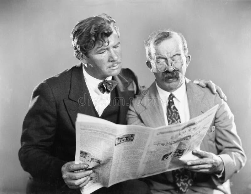 Zwei reife Männer, die zusammen eine Zeitung lesen (alle dargestellten Personen sind nicht längeres lebendes und kein Zustand exi lizenzfreie stockfotografie