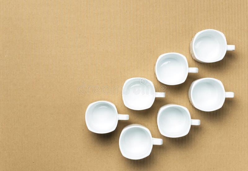 Zwei Reihen des weißen hellbraunen Hintergrundes der Kaffeetassen lizenzfreies stockbild