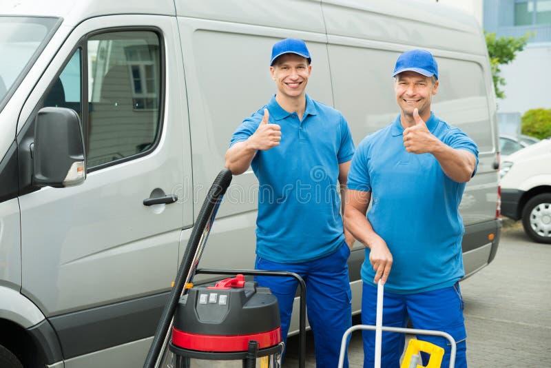 Zwei Reiniger, die mit Reinigungs-Ausrüstungen stehen lizenzfreies stockfoto