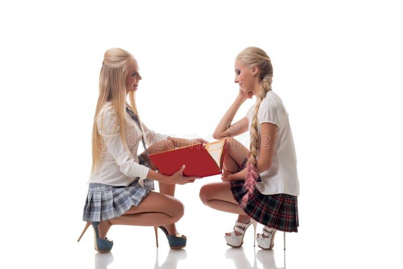Zwei reizende blonde Schulmädchen, die im Studio aufwerfen lizenzfreies stockfoto